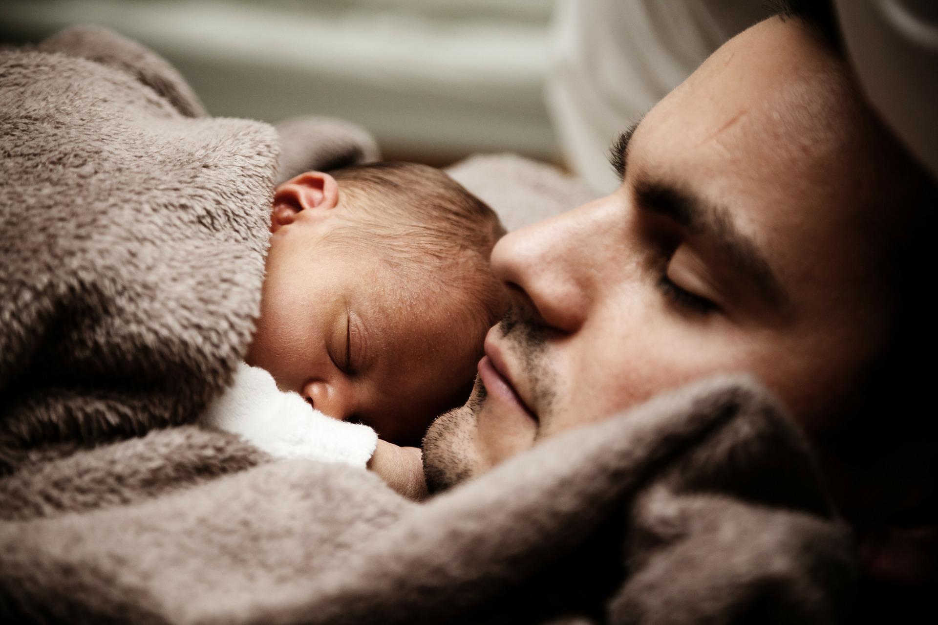 un bébé allongé sur son papa